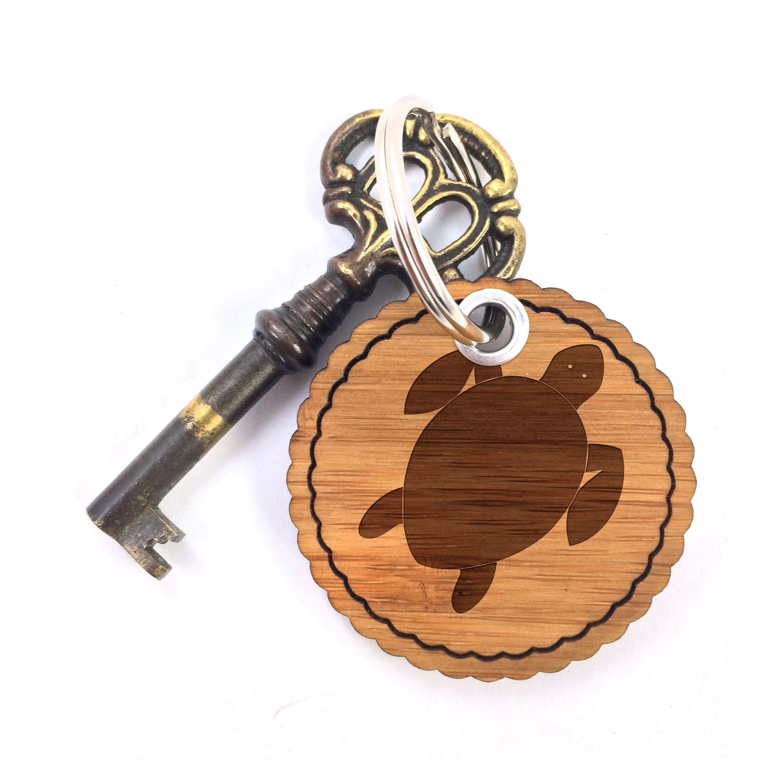 Rundwelle Schlüsselanhänger Schildkröte aus Bambus  Coffee - Das Original von Mr. & Mrs. Panda.  Ein wunderschöner Schlüsselanhänger aus dem Hause Mr. & Mrs. Panda    Über unser Motiv Schildkröte  Schildkröten gelten als besonders gemütliche Tiere, die schon länger Erdbewohner sind als wir Menschen. Sie können bis zu 100 Jahre alt werden.    Verwendete Materialien  Bambus Coffee ist ein sehr schönes Naturholz, welches durch seine außergewöhnliche Holz Optik besticht und sehr edel und…