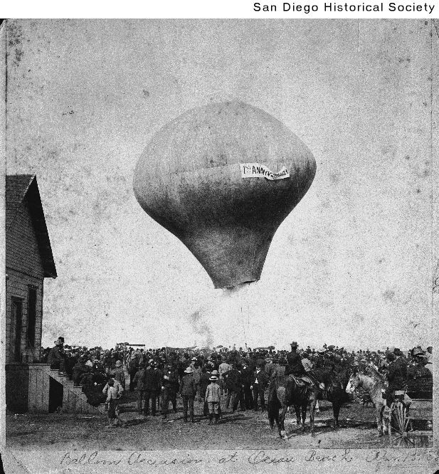 An early hot air balloon rises over a crowd during the