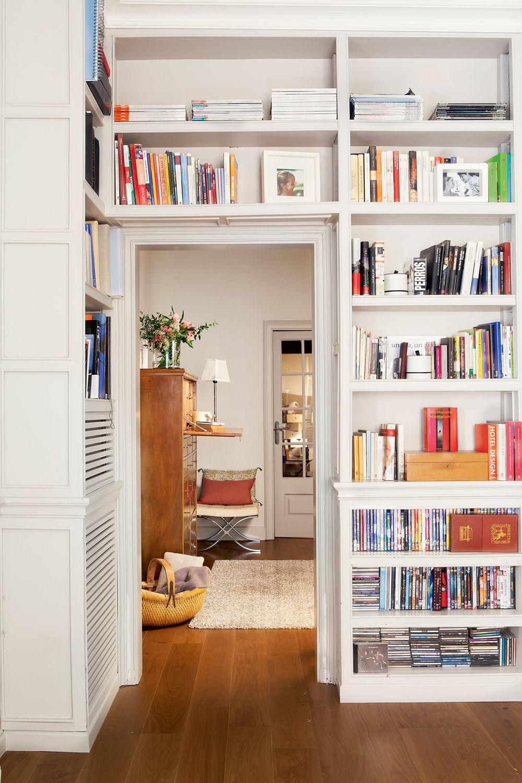 Librera blanca alrededor de una puerta con escritorio al
