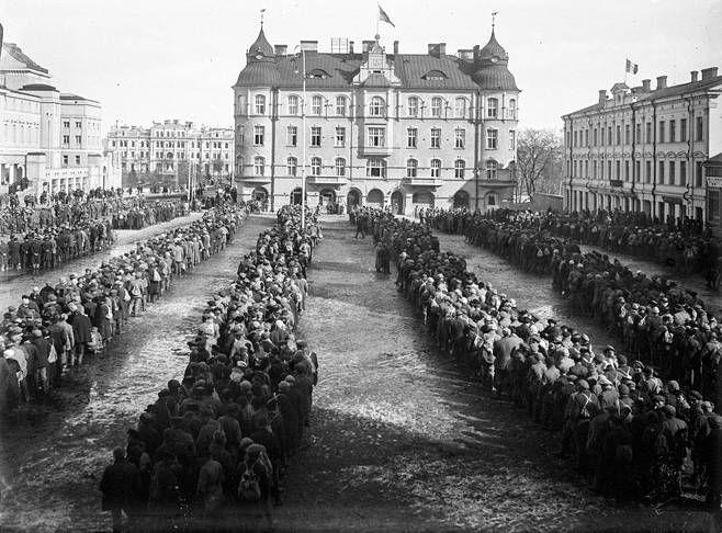 Punavankeja Tampereen Keskustorilla 6.4.1918. Oikealla olevan Selinin talon katolla liehuu Italian lippu ja taustalla Sumeliuksen talossa Ruotsin lippu.