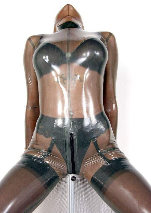 Transparent latex catsuit over black stockings, suspender ...