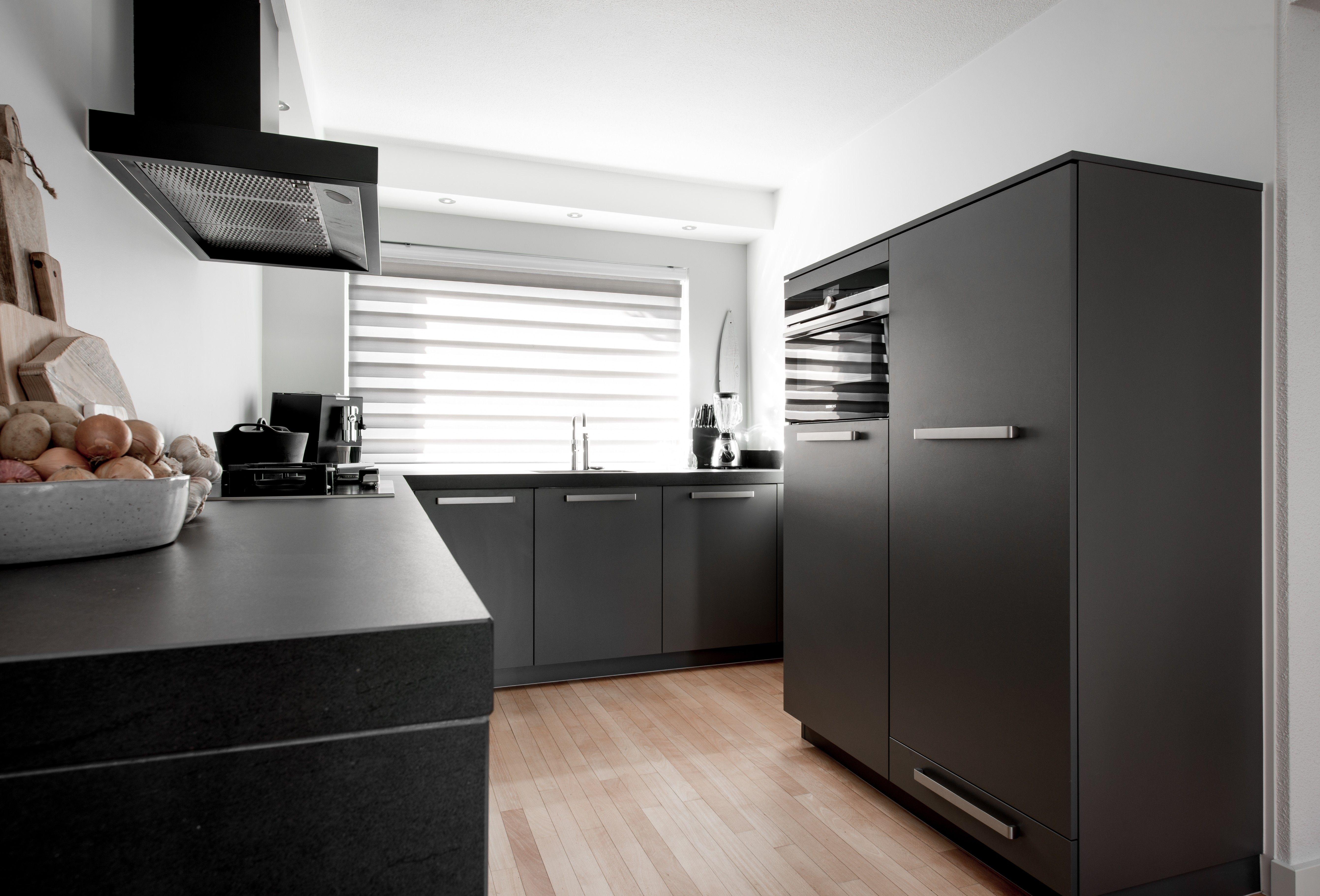 Fusion Design Keuken : Een donkergrijze keuken met witte wanden zwarte apparatuur en een
