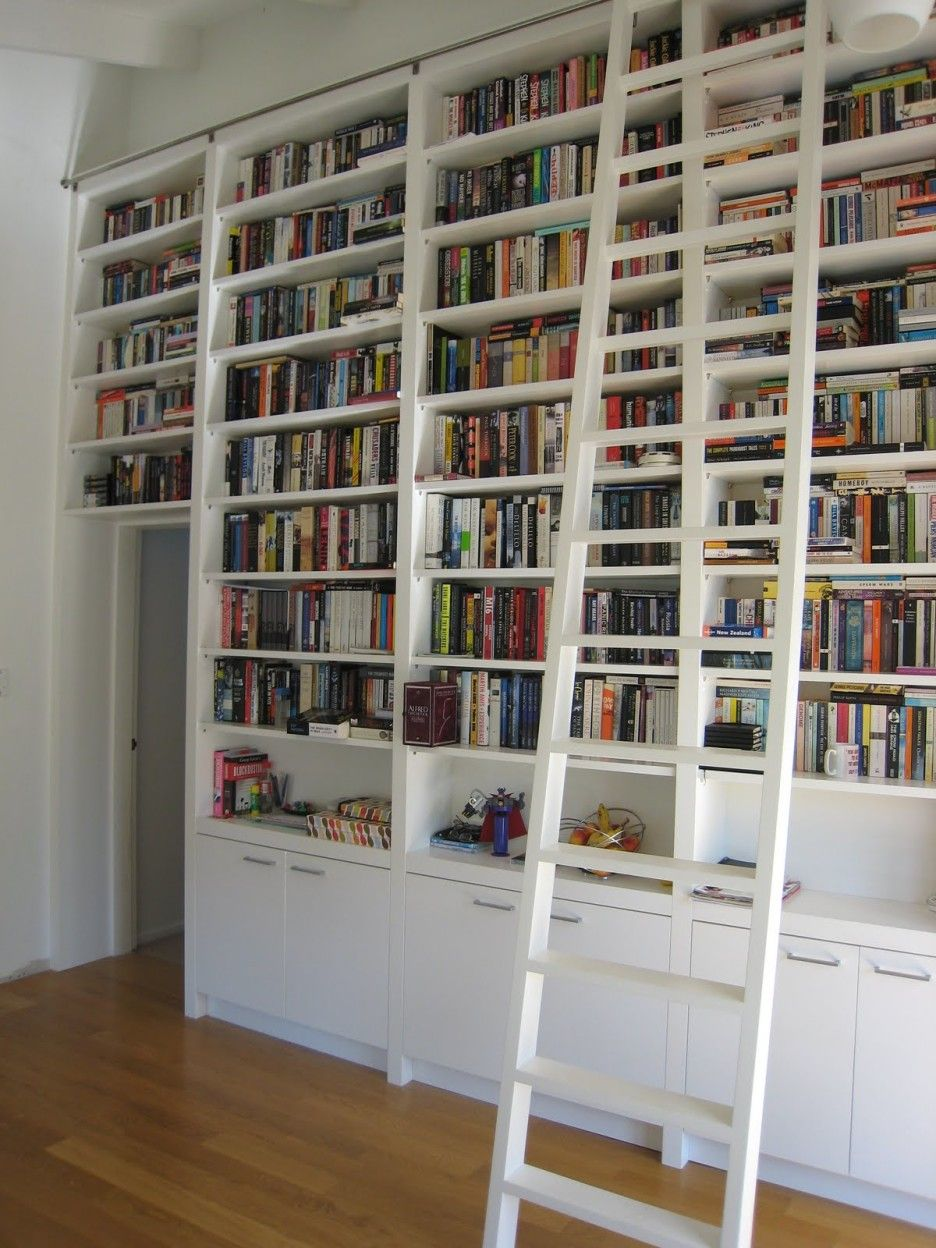 Tall White Wooden Bookshelf With Ladder On Brown Floor Modern As The Main Furniture For Home Library