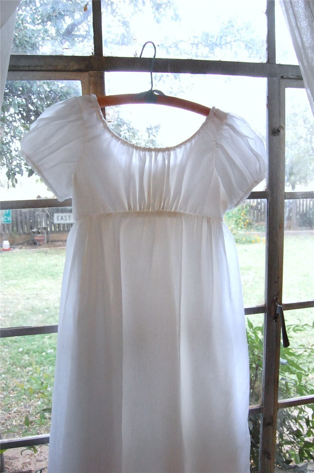 A white cotton voile regency drawstring dress for a year old girl