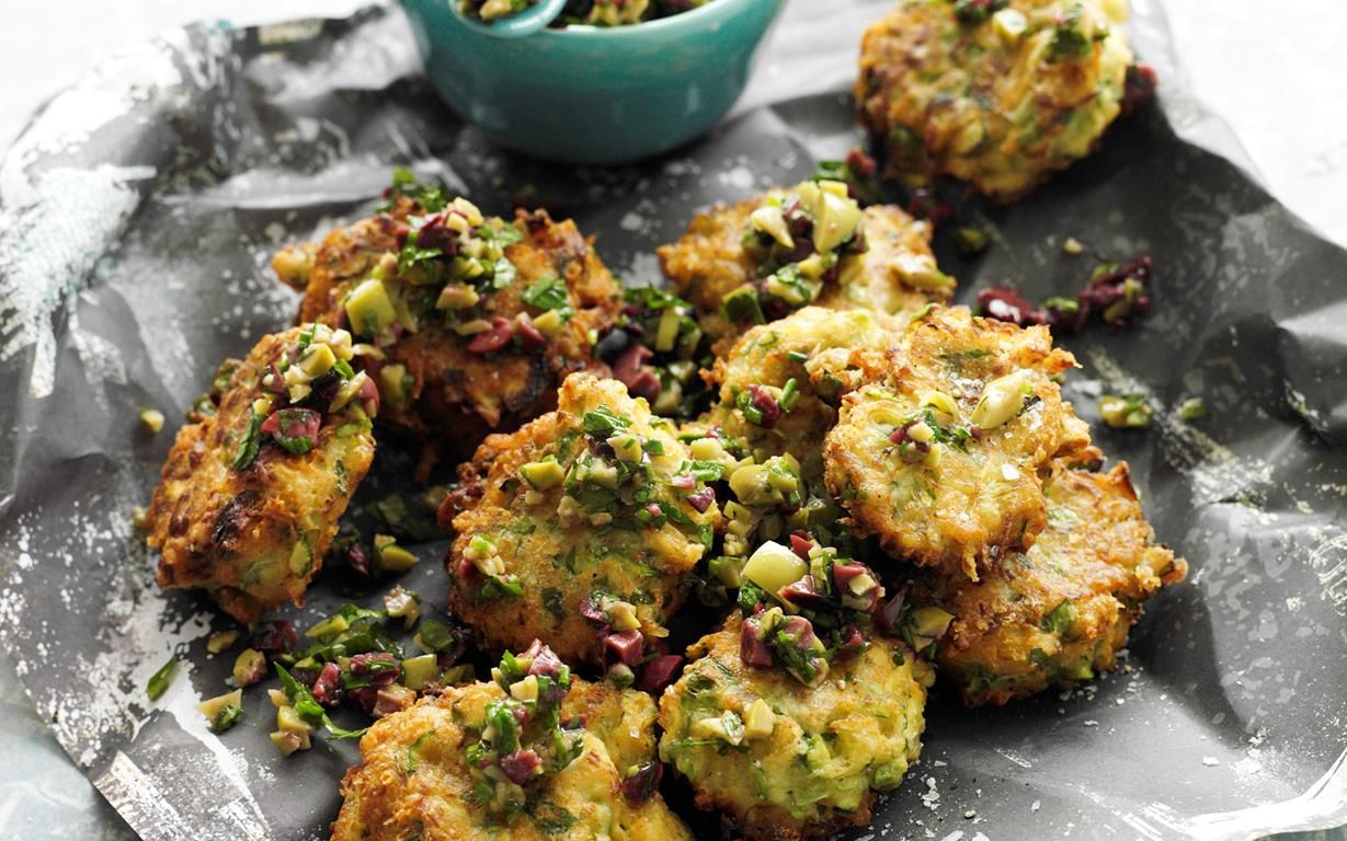 Artichoke and asparagus fritters with olive relish recipe - By Australian Women's Weekly, These delicious golden artichoke and asparagus fritters are perfect served hot with a fresh tangy olive relish. They make a brilliant finger food or starter for your next dinner party.