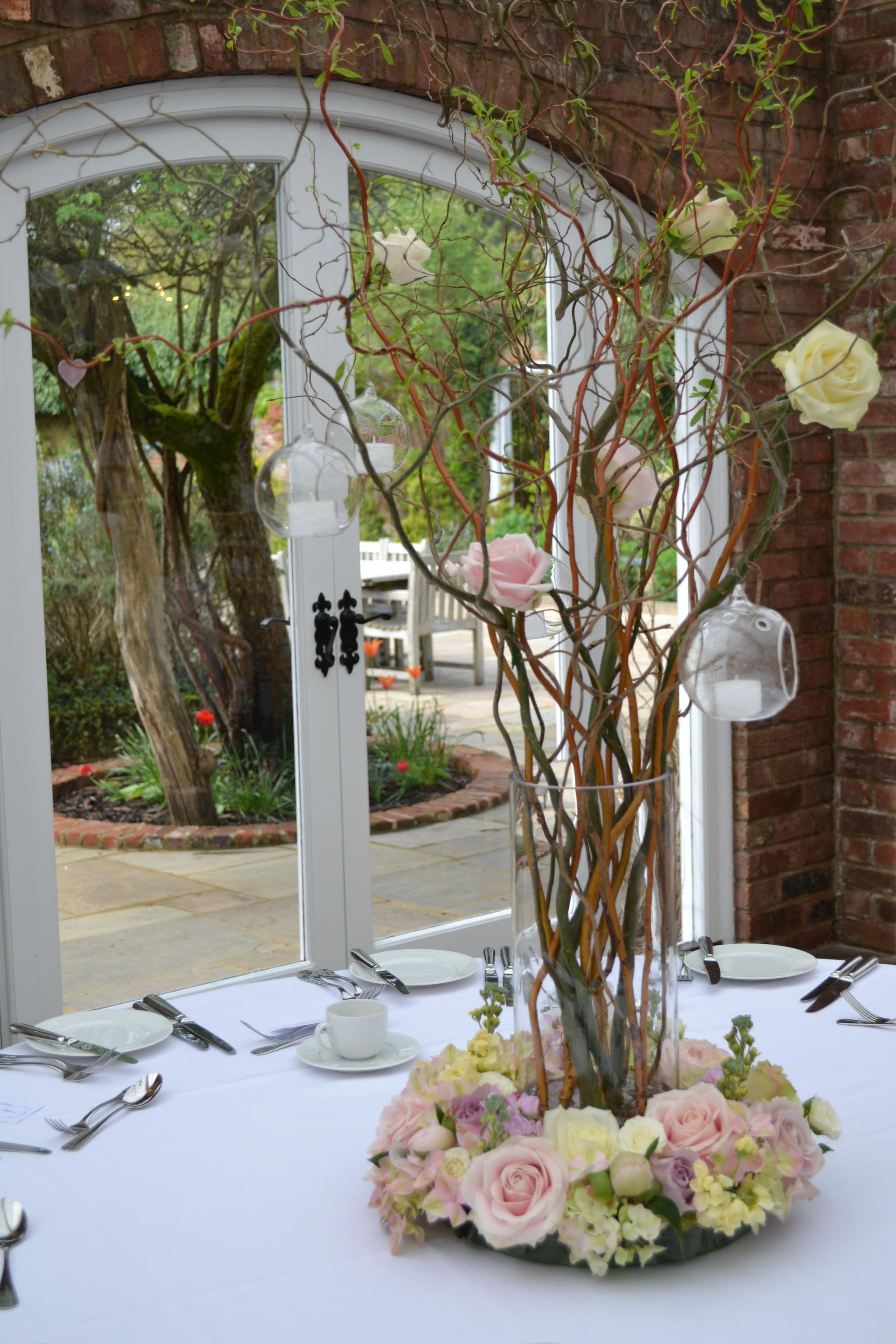Tall Vases Containing Contorted Willow Decorated With Sweet Avalanche And Avalanche Roses And Glass Balls Containing Tea Lights Wedding Centerpieces Tall Vases Flower Arrangements