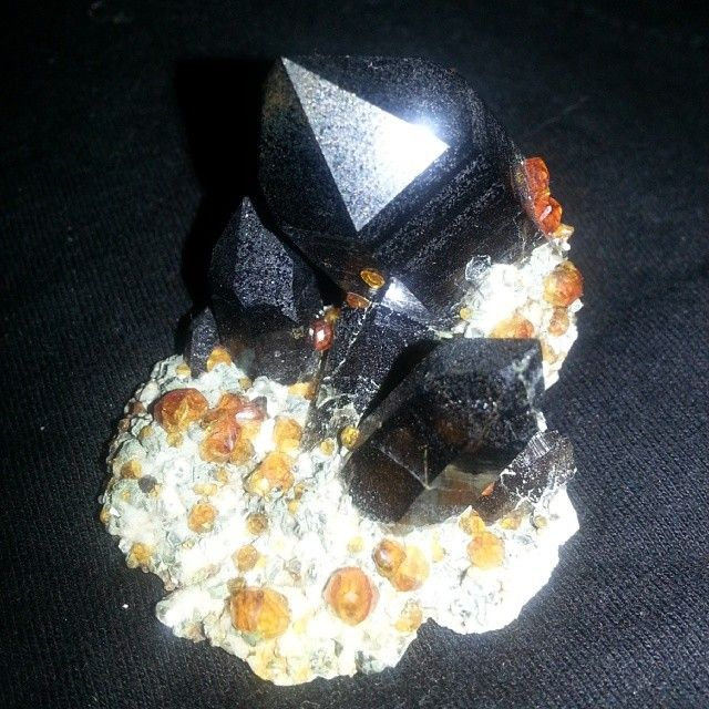 the most BEAUTIFUL smoky quartz formation I have ever seen! also extremely dark smoky quartz! amazing! and the little orange crystals on it should be garnets... may be small but it's just breathtaking