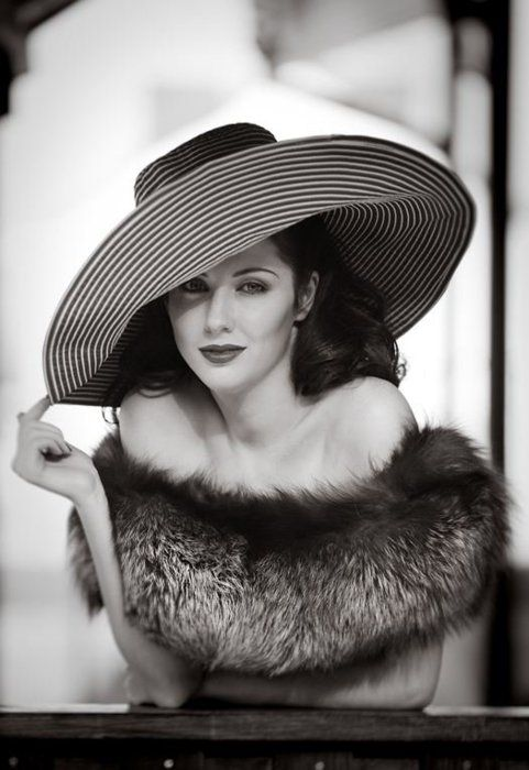 black and white photo of women in fur and big hat old