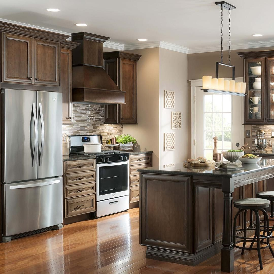 Classic elements and rich wood tones add sophistication to this kitchen, while open prep space makes multitasking a breeze. Click the link in profile to shop this look!  #lowes #kitchen #inspiration