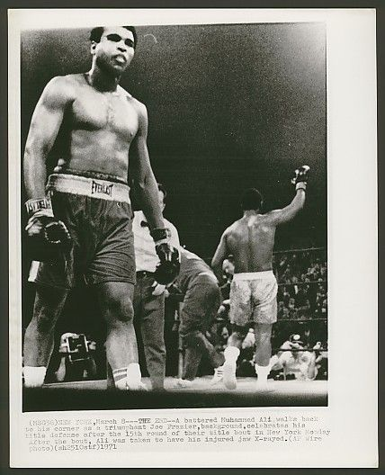 "Philly Legend, Joe Frazier.    ""A battered Muhammad Ali walks back to his corner as a triumphant Joe Frazier, background, celebrates his title defense after the 15th round of their title bout in New York. Monday after the bout, Ali was taken to have his injured jaw X-rayed.""    For more Philly support, check http://VeteransShirtium.com !"