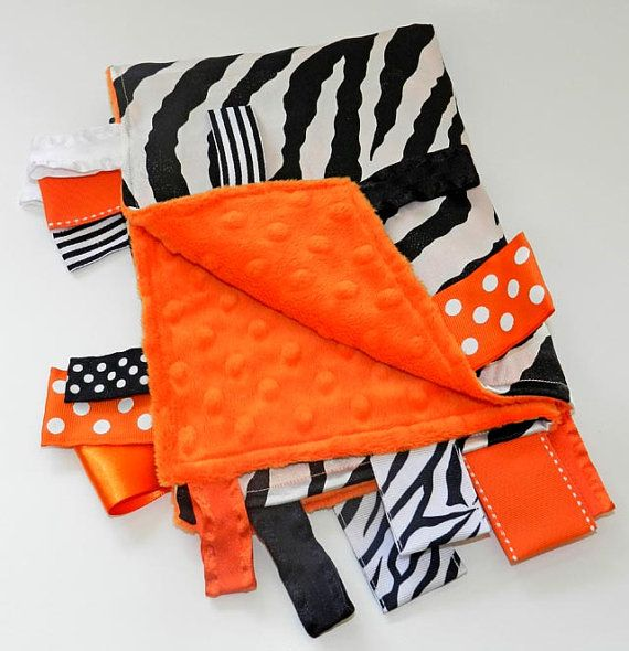 Silky Satin White Zebra Stripes and Minky Orange Dot Ribbon Tab Sensory Blanket for Babies. Has Ribbon Tags for play and chewing.  Comes in Orange, Turquoise, Red, Green or Pink backing/accents.