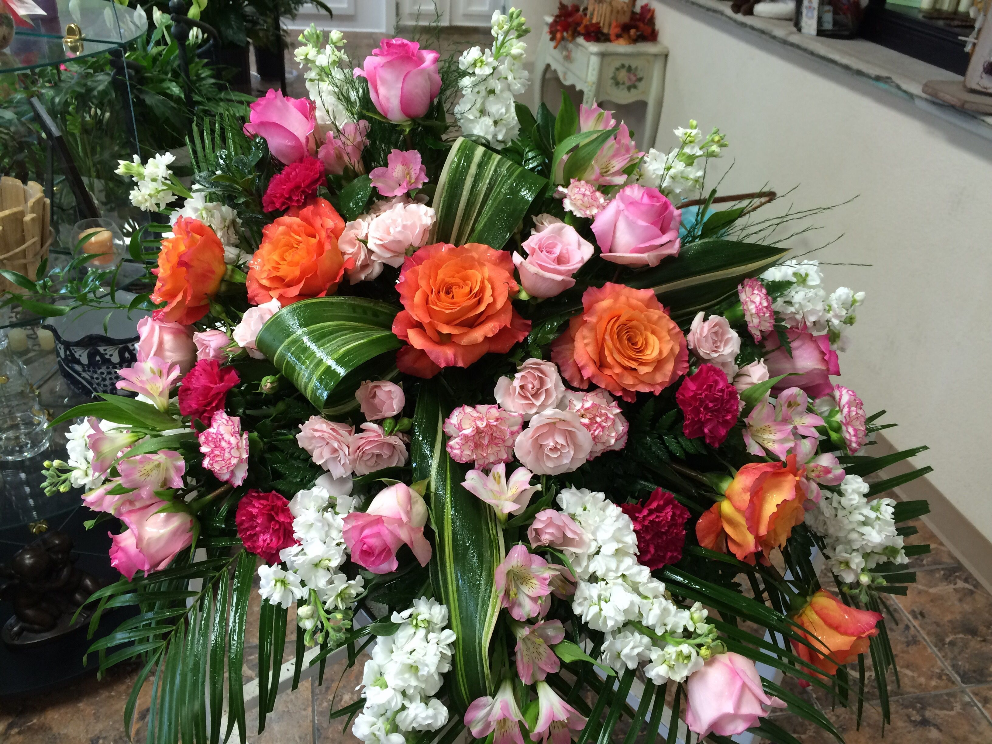 "Casketspray by Cyndy Smith of our ""free spirit"" roses, pink roses, pink spray roses, pink, hot pink & bi-color carnations, pink alstroemeria, white stock, aspidistra bow & greenery"
