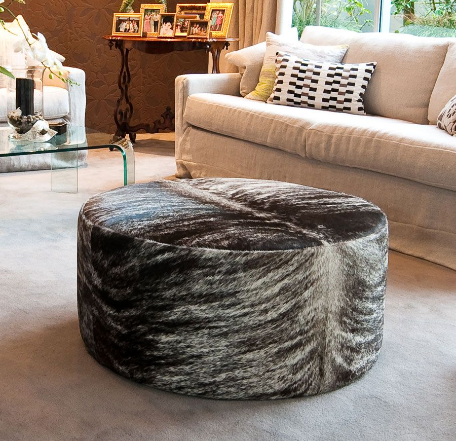 A trendy taupe round cowhide ottoman by Gorgeous Creatures who are a ...