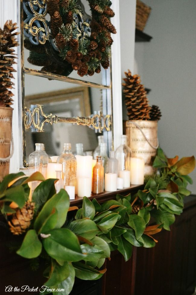 Christmas Mantel With Magnolia Garland Bottles And Candles