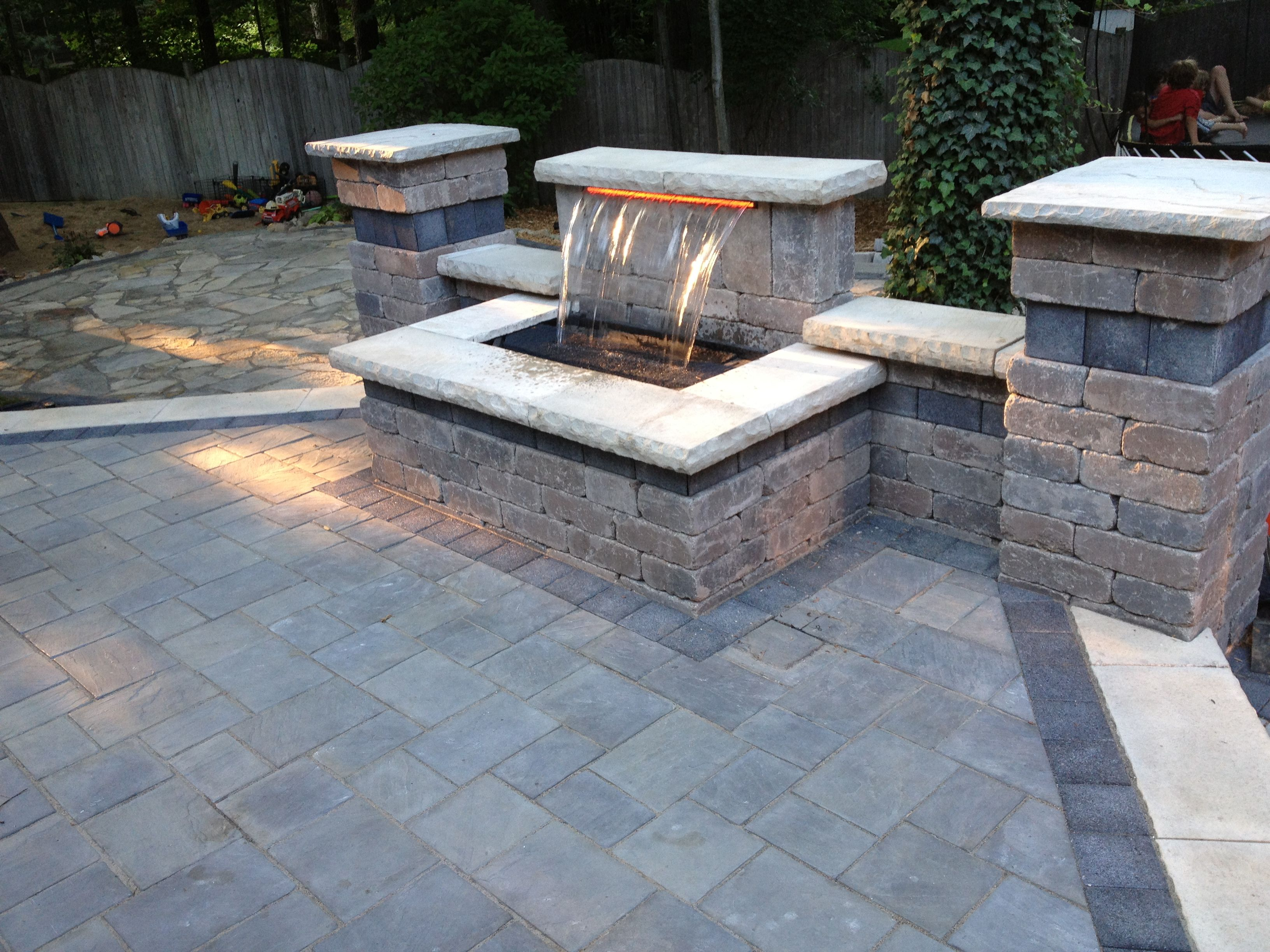 Beautiful waterfall and raised patio using Unilock brick pavers
