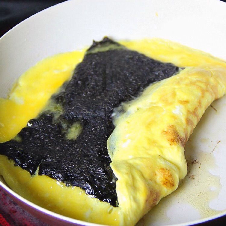 Using a spatula, lift one end of the egg and fold few inches inside & over seaweed.