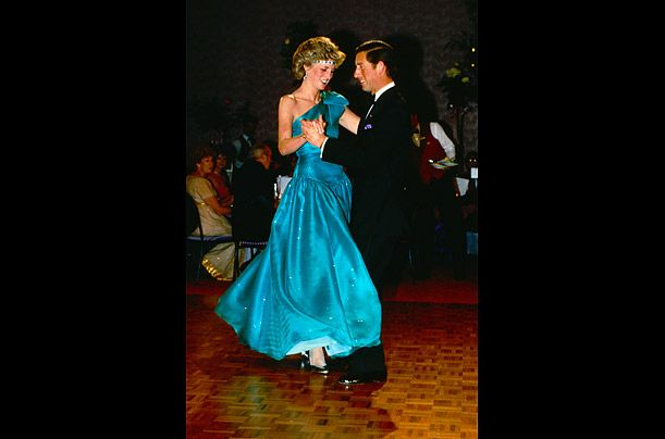 Tiny Dancer ~ The prince and princess take to the dance floor in the early 1980s.  Diana accessorized her blue dress with a bold jeweled headband.