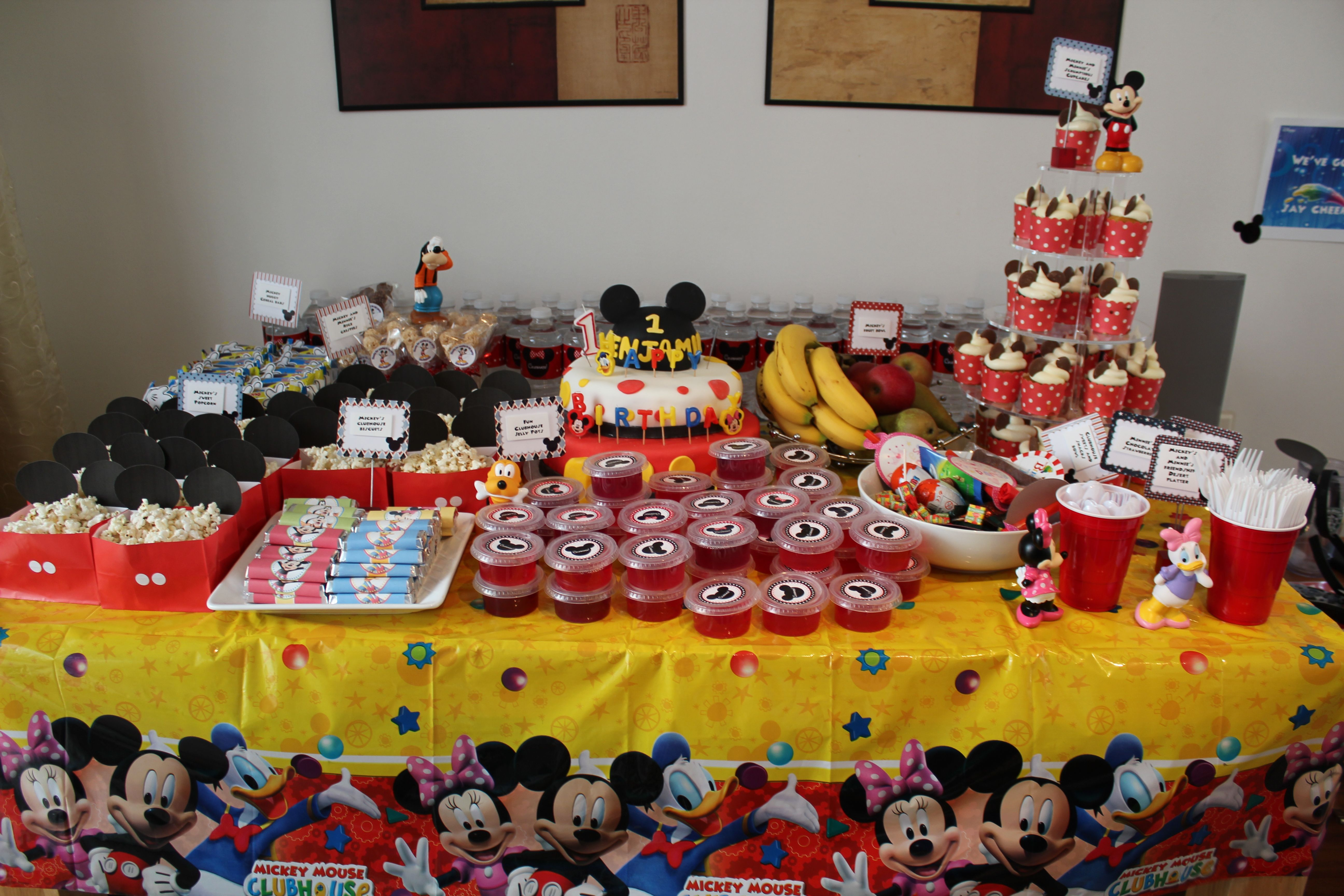 Complete table of cakes, goodies and sweets. Mickey bags with popcornjelly pots Mickey shaped rice crispies Mickey and friends chocolate biscuit bars Mickey water bottles Mickey