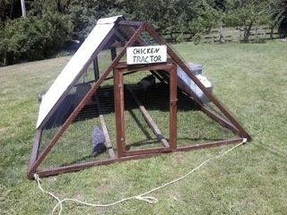 a frame chicken tractor with wheels and rope handle