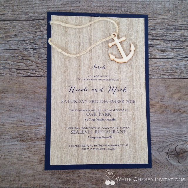 Nautical wedding invitation featuring navy cardstock, wood paper and embellished with a wooden anchor and rope. Handmade by White Cherry Invitations