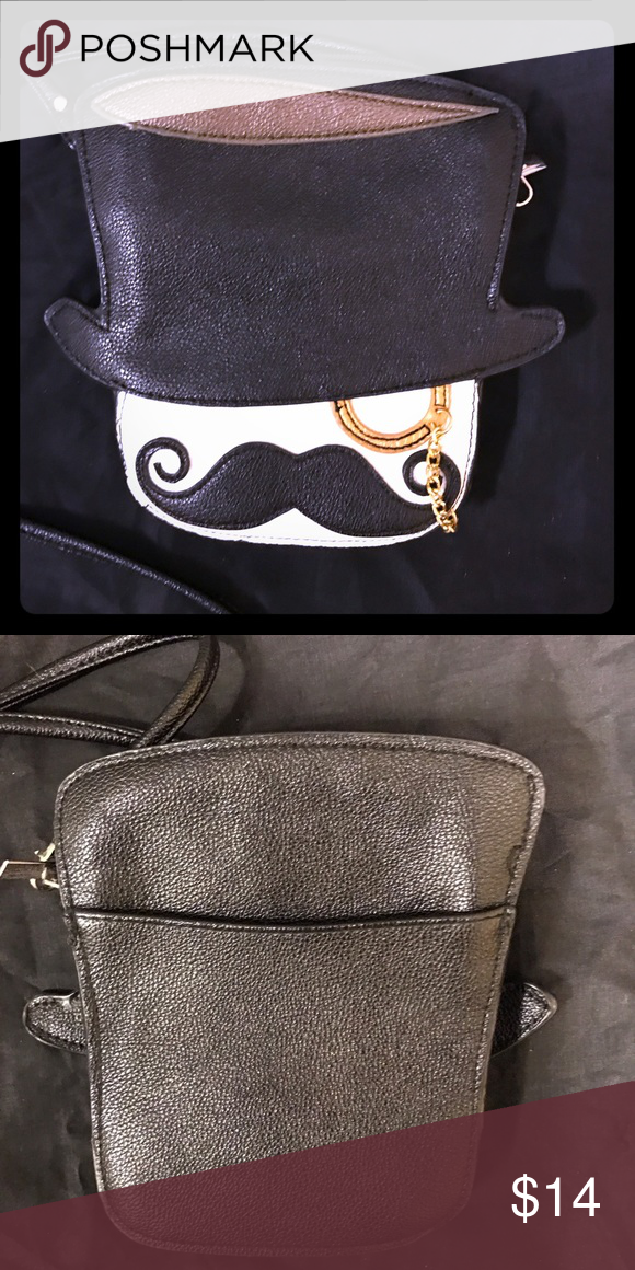 Funny Quirky Mustache Top Hat Monocle Man Purse Super fun quirky purse from ModCloth of a little top hat wearing monocle man with a mustache. Has a cute gold chain for the eye wear. Brand Far Nine, zipper closure, removable shoulder strap. It's about 7 inches by 6 inches and I stretched about 1.5 inches wide. Good for carrying around wallet, phone, keys, your favorite lipstick, a pair of sunglasses. The fabric lining on the inside is gone from one side. Does not take away from the…
