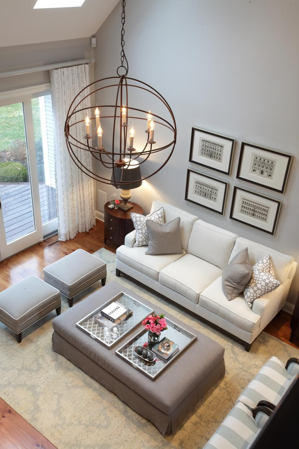 High ceilings and stylish design this living room uses a beautiful palette of soft gray and white an orb chandelier and black and white framed art