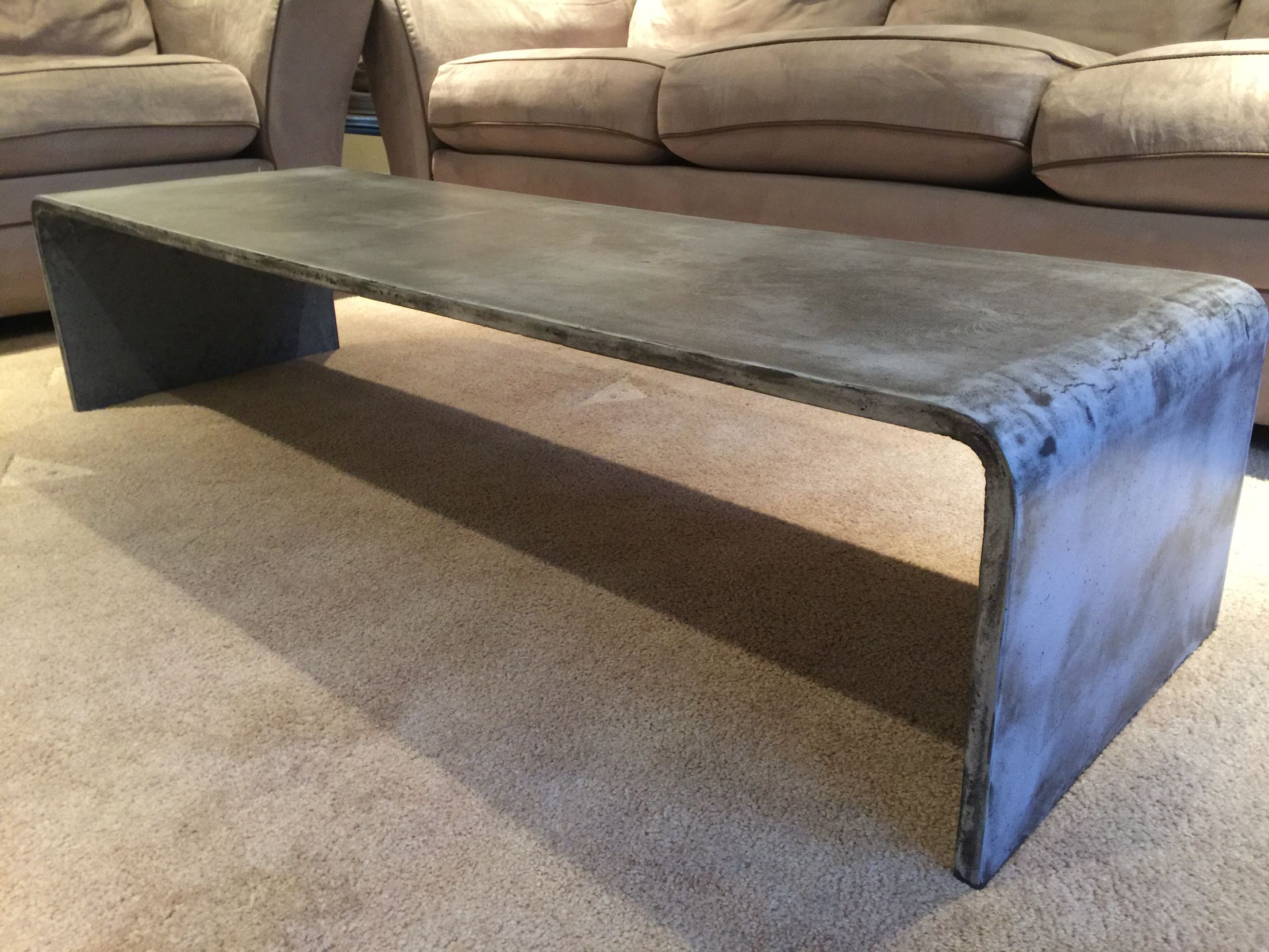 low profile bent concrete coffee table custom built by dudley