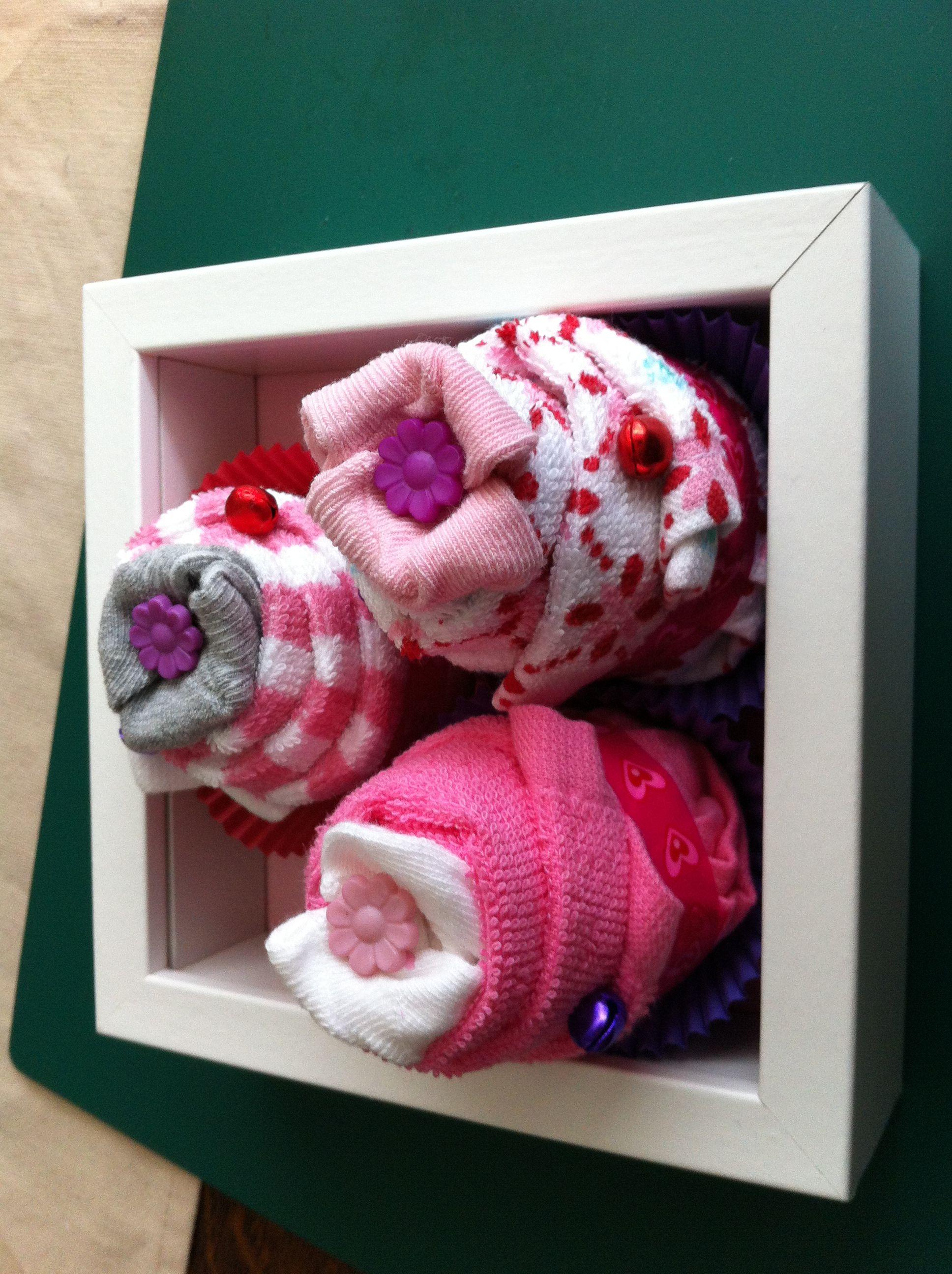 DIY cupcakes: gemaakt van 3 paar sokjes gewikkeld in 3 monddoekjes. Voor de versiering heb ik paperclips gebruikt om de bloemen en belletjes in de cupcake vast te steken. Leuk als kraamcadeau of voor bij een baby shower. De cakejes staan nu in een fotolijstje maar je kunt ze natuurlijk overal in doen.