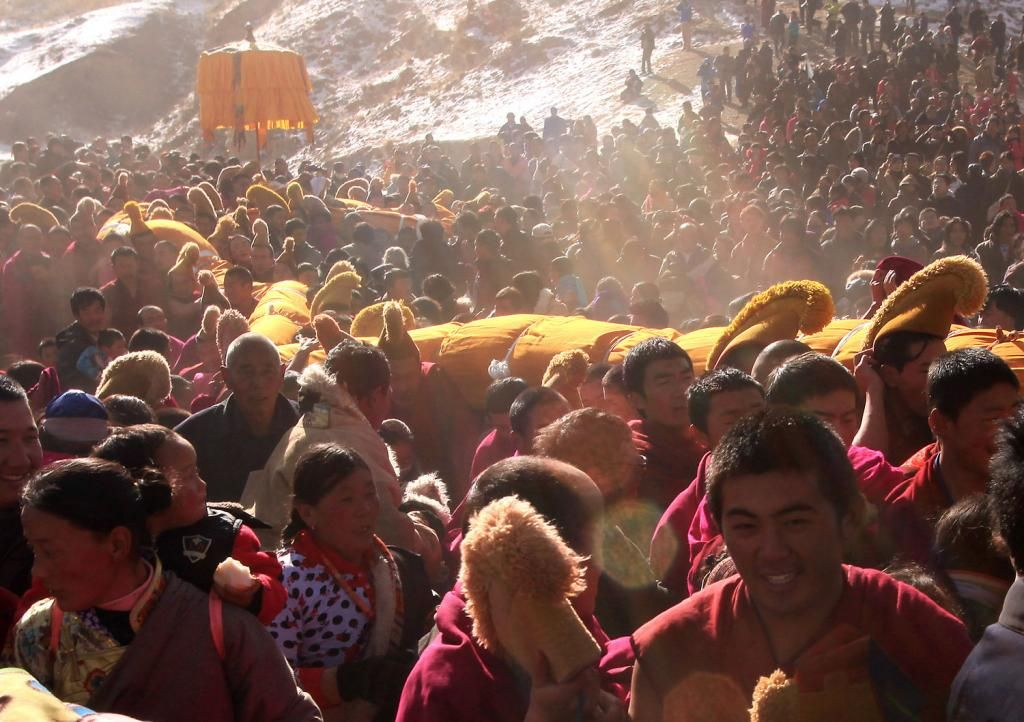 """Tibetan monks carry a giant Thangka of Buddha, or tapestry, back to the Labrang Monastery, the largest Tibetan monastery outside of Lhasa, during the Tibetan Monlam Festival in Xiahe, a small town in Gansu Province on the Tibetan plateau, February 4, 2012.  Thousand of Tibetan monks, pilgrims and nomads have converged on the monastery for the annual """"Sunning of the Buddha"""" ritual, in which the world's largest Thangka of Buddha (90ft in length, 40ft in width) is unveiled at first light on…"""