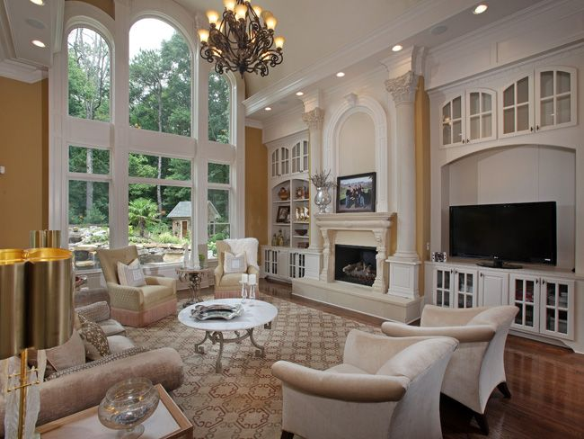 Living Room With High Ceiling Fireplace And Built In Cabinetry