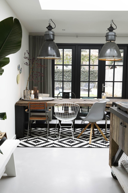 Industriële eetkamer met een houten tafel en verschillende stoelen ...
