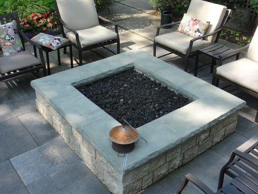 A Square, Modular, Gas Fired Fire Pit In An Ashlar Pattern Bluestone Patio.  Its Shape Reinforces The Clean Lines Of The Paving.