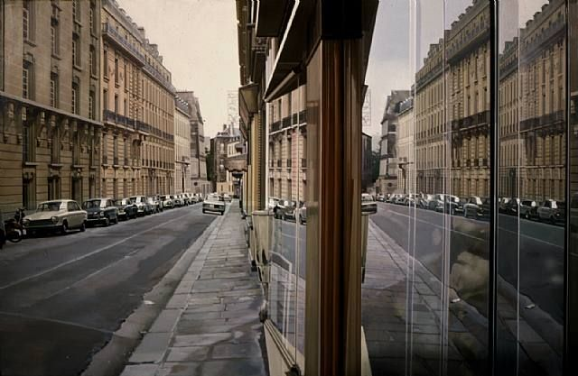 Paris Street Scene, a painting by American artist Richard Estes, depicts the art genre known as Photorealism or Superrealism.  The work of Photorealists was inspired mostly by photographs and look incredibly life-like.  The use of the airbrush to create these paintings helped to give them the look of glossy photographs.  Richard Estes is considered one of the best Photorealist artists due to his eye for detail.