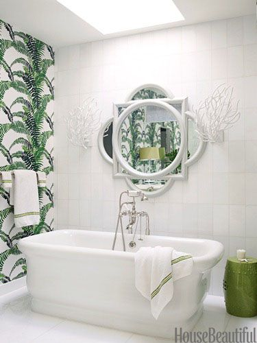 Determined not to decorate this Oyster Bay, New York, beach house with predictable blue and white, designer Christina Murphy chose citrus green instead. In the master bath, a freestanding Empire tub by Waterworks is positioned under a skylight. Fern wallpaper by Spring Street Designs creates an instant tropical rain forest.