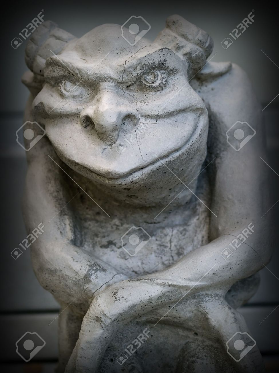gargoyle statue emphasis on face and eyes with a dark border stock
