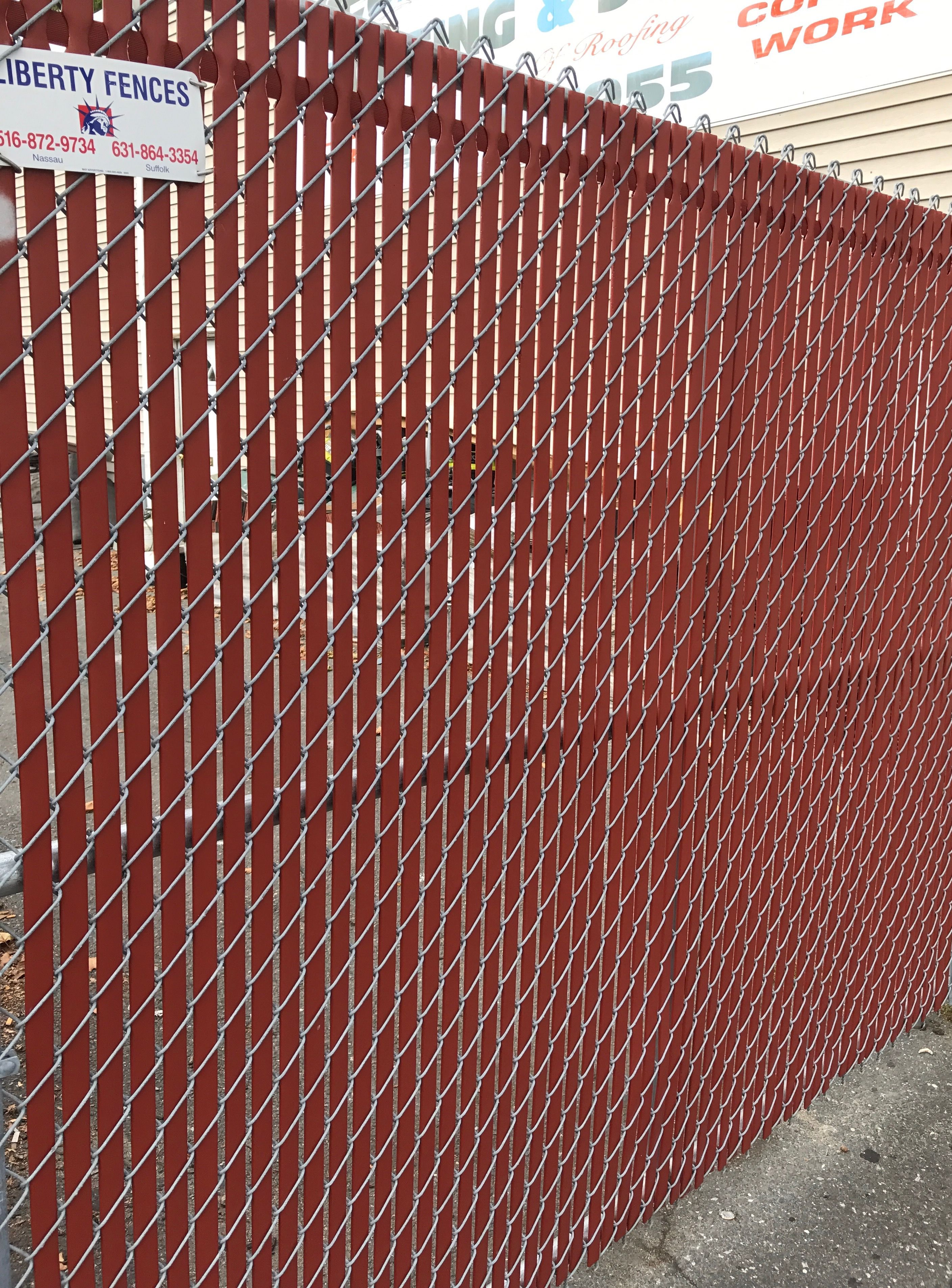 Chain link fence with red PVT slats installed in Franklin