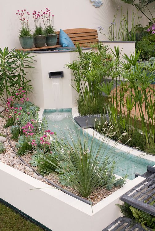 Waterfall in modern water garden with raised beds Modern flower beds
