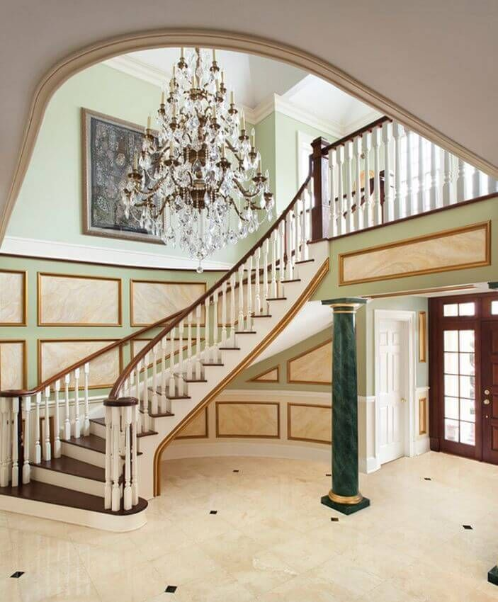 An incredible ornate foyer with a curving staircase green marble columns and a wealth