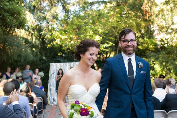 Bride with updo and groom in navy exit from wedding ceremony