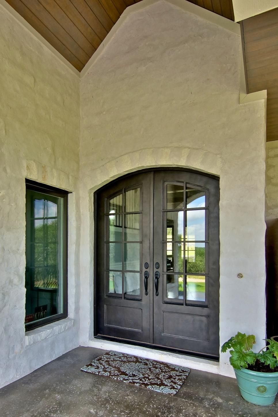 This home's entryway boasts a gorgeous stone exterior and arched doors, accomplishing a classic French country look.