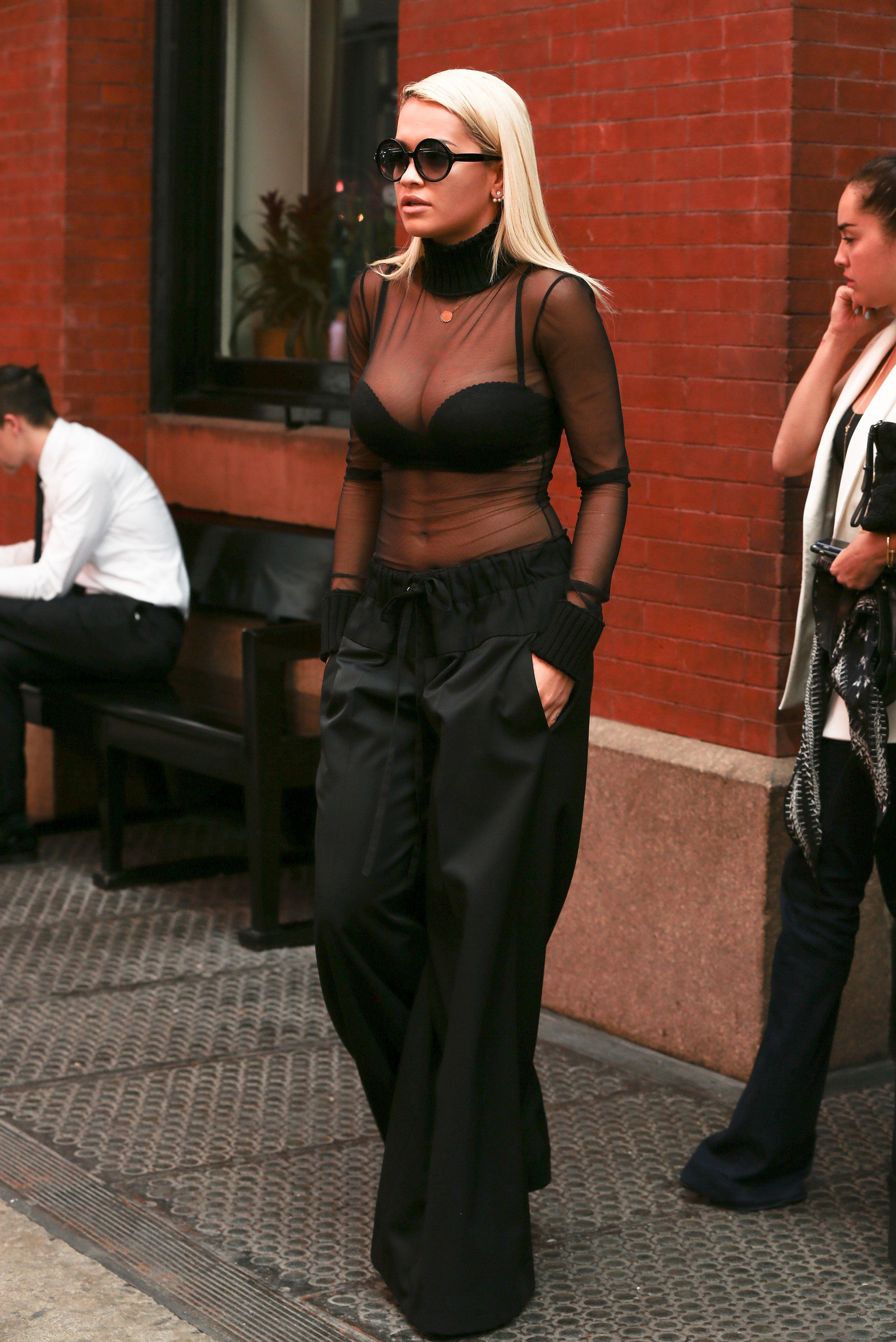 Rita Ora showed off her scalloped black bra — and lots of cleavage — under  her sheer turtleneck. She finished her outfit with black tie-waist pants  and some ... c68027b67