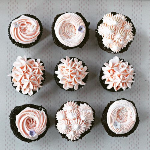 """Pink vanilla buttercream on dark chocolate cuppies."