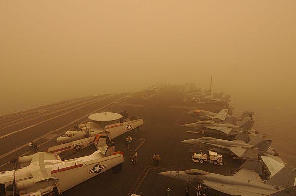 The Nimitz-class aircraft carrier USS Carl Vinson (CVN 70) passes through a sand storm.
