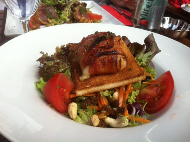 Goats cheese wrapped in bacon on toast served on a bed of mixed salad leaves, carrots, sultanas, tomatoes and cashew nuts.
