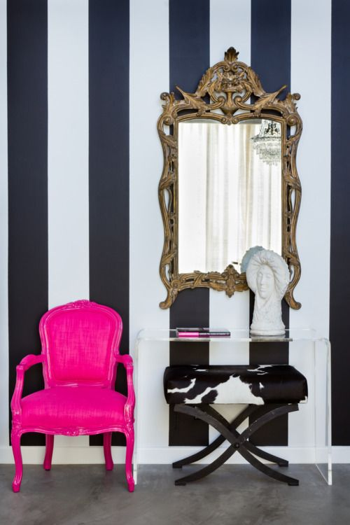 Black And White Striped Wall, Neon Pink Chair, Ornate Gold Mirror, And Cow