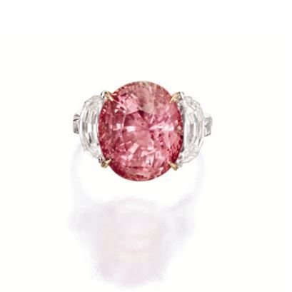 PADPARADSCHA AND DIAMOND RING. Centring on an oval padparadscha sapphire weighing 11.99 carats, flanked on each side by a half moon-shaped diamond together weighing approximately 1.50 carats, mounted in 18 karat white and pink gold. | Sotheby's