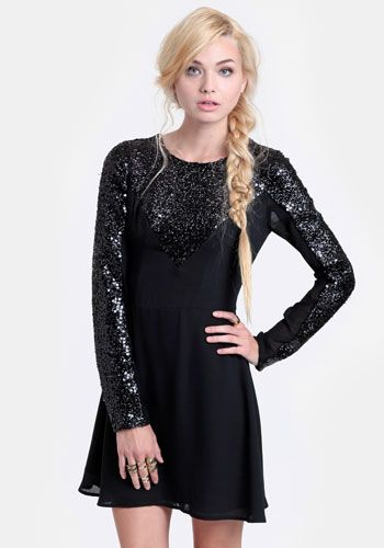 e05af7d6de44 Black chiffon fit-and-flare dress featuring glossy black sequins and semi-sheer  sleeves. Finished with an exposed back zipper closure. Fully lined.