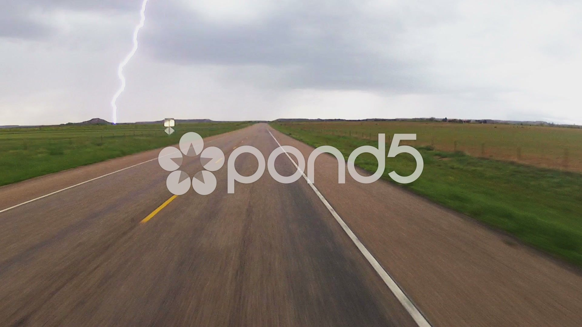 Driving west texas road with lightning strike ahead