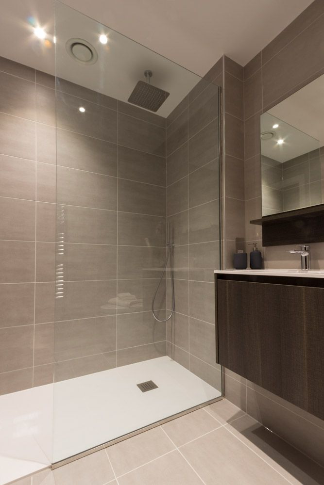 A modern central London apartment bathroom design. Featuring neutral grey  tiles, luxurious white porcelain