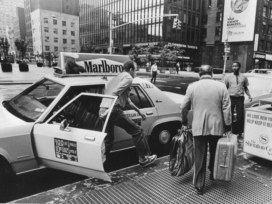 A taxi driver parked in front of the Sheraton New York Times